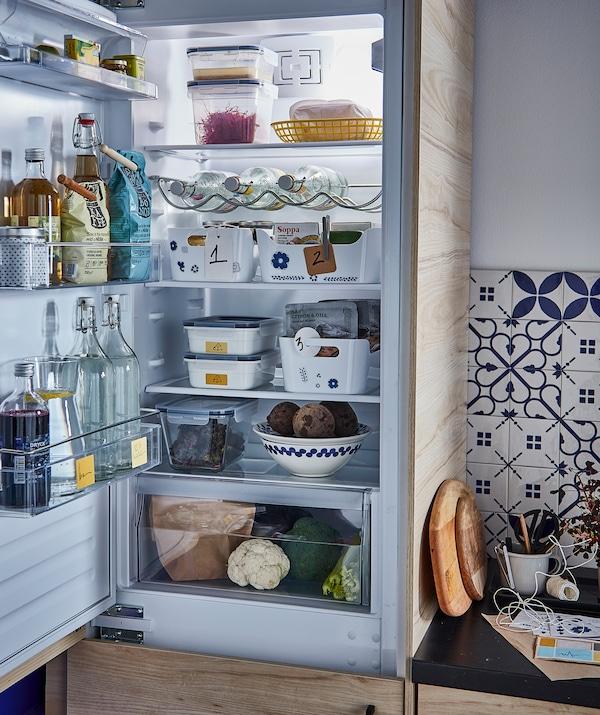 ثلاجة مفتوحة وبداخلها طعام وشراب: زجاجات في الباب، أواني على الرفوف، ودرج للخضروات في الأسفل.