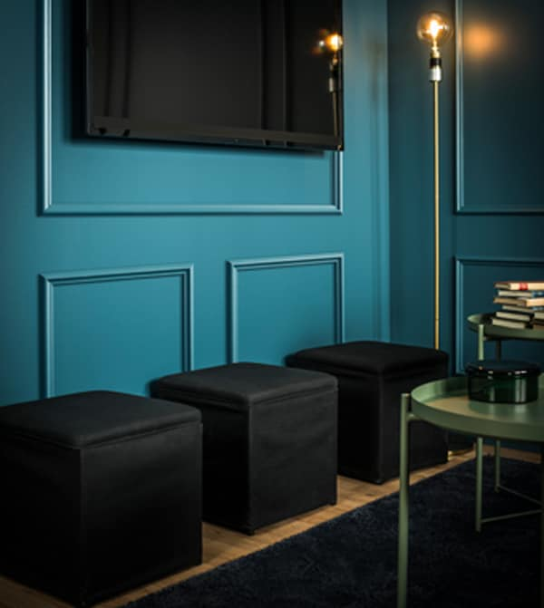ثلاثة مقاعد منخفضة أسفل تلفزيون معلق على الحائط.