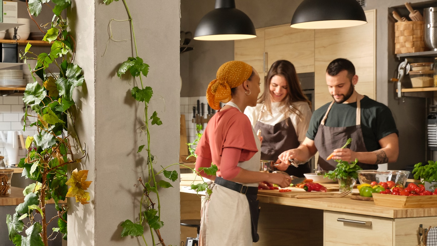Three aproned people stand by a large kitchen island in a spacious kitchen, preparing food. Plant vines line a nearby post.