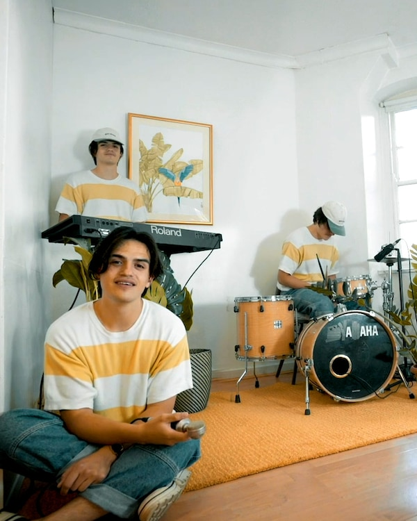 Three band members preparing to make music in a white walled room.