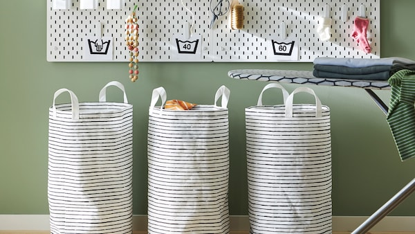 Three black and white striped laundry bags placed against a green wall, below a white pegboard with hooks.