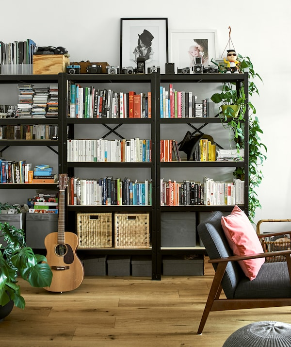 Three black bookcases filled with colour co-ordinated books, wicker baskets, framed photos, vintage cameras and plants.