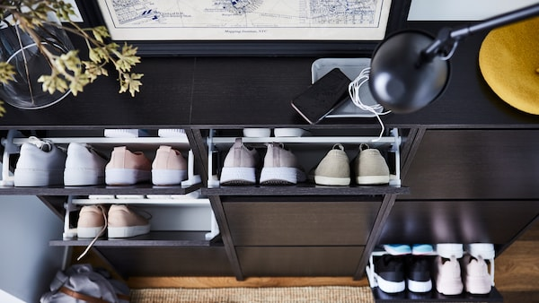 Three black/brown BISSA shoe cabinets with three compartments with several pairs of shoes inside the open compartments.
