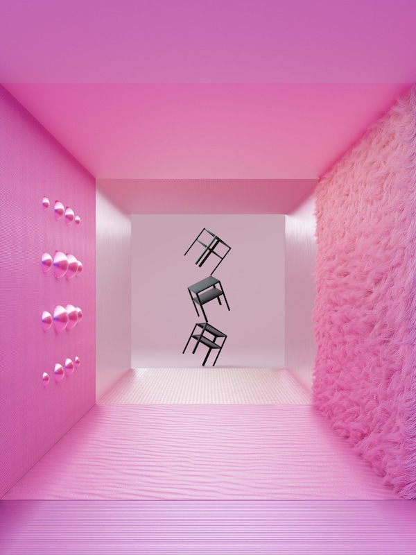 Three, black, KNARREVIK bedside tables balance on top of each other, one-legged, at the end of a pink corridor.