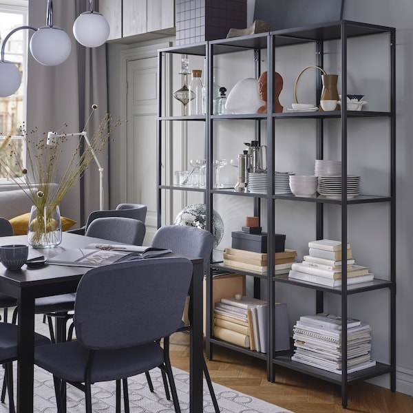 Three black shelving units stand together to create a larger shelving unit. Dinnerware and decorative items are stored here.