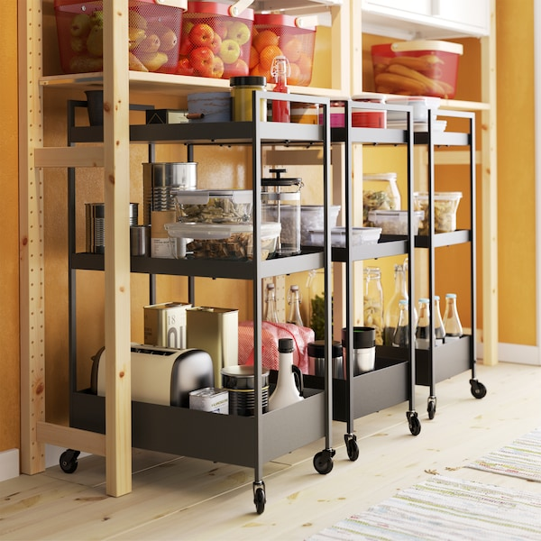 Three black trolleys with castors stand under a shelving unit in pine, and the trolleys store food and kitchen appliances.