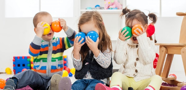 Three children sitting and play with colorful balls