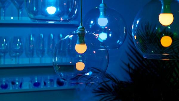 Three clear glass pendant light fixtures with lit lightbulbs inside.