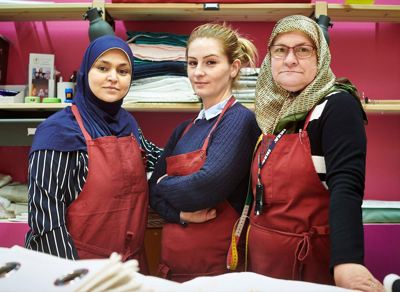 Three confident women posing at the fabrics department of an IKEA store in honor of World Refugee Day on June 20th.