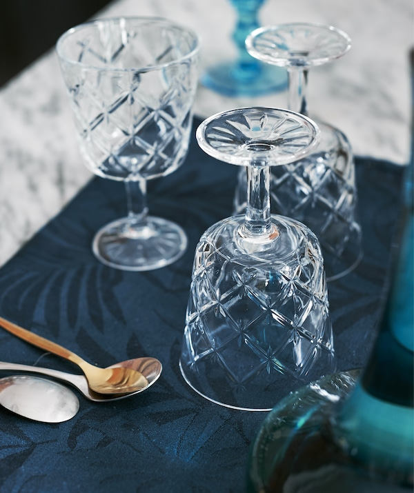 Three cut-glass wine glasses on the dining table.