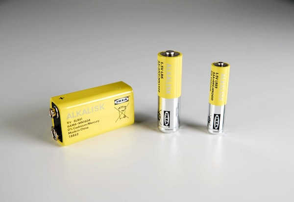 Three different sized yellow IKEA batteries sitting on a neutral gray surface.