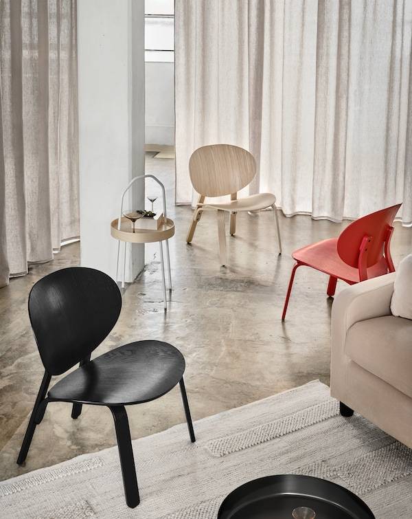 Three FRÖSET chairs in white, red and black stained oak veneer standing in a haphazard way near a sofa.