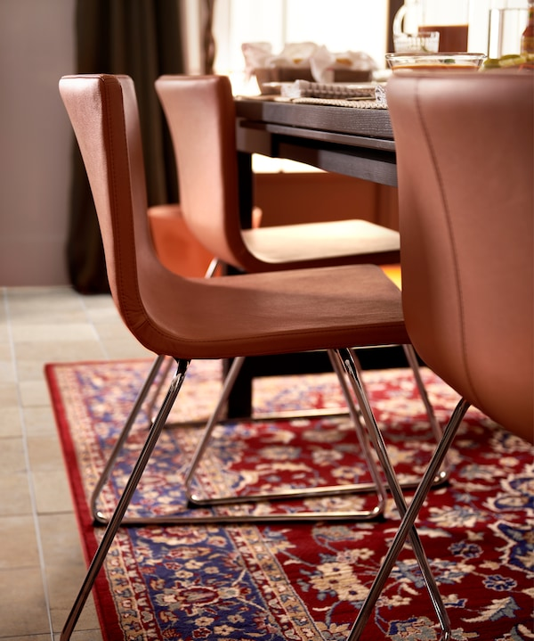 Three golden-brown leather chairs with chrome-plated legs, a black table and a multi-coloured oriental-patterned rug.