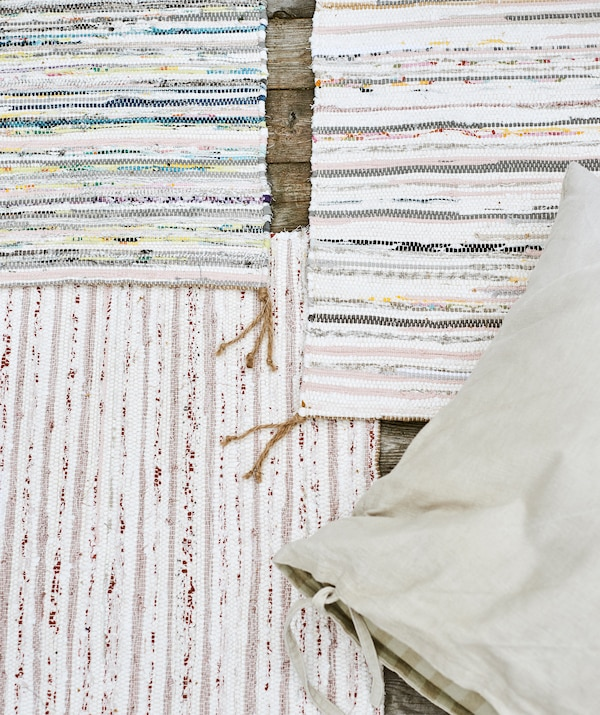 Three handwoven multicoloured striped rugs overlapping each other on wood decking, with a beige linen cushion on top.