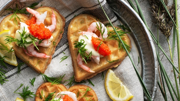Three heart shaped VÅFFLOR waffles with shrimps, mayonnaise, seaweed pearls and dill on a plate with a kitchen towel.