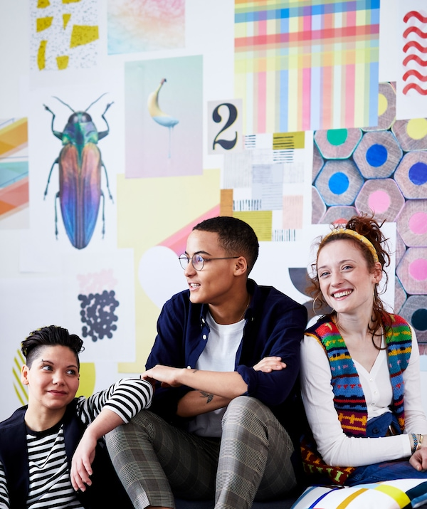 Three housemates sit together against a wall covered in vibrant images.