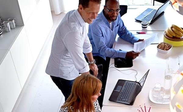 ثلاثة من العاملين في ايكيا في غرفة مكونة من مكتبين برتقالي مع كراسي، وخزانة ذات أدراج ورفوف جدارية مفتوحة.