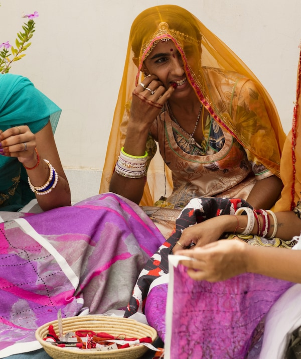 Three Indian artisan women sitting and working on colourful fabrics for the IKEA ANNANSTANS collection together.