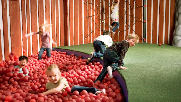 Three kids are playing and two are going out in the Smland ball pool, full of play and fun. A child is hanging on a spider web.