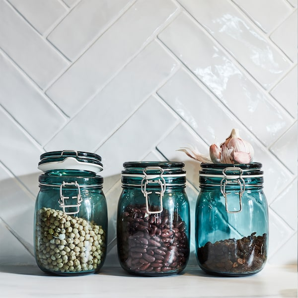 Three KORKEN jars in green see-through glass help preserve aromas and flavours. Dried raisins and beans are stored inside.