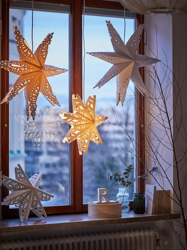 Three lamps with STRÅLA lampshades in the shape of snowflakes hang in a window. Another one is on the windowsill.