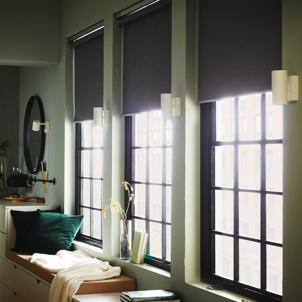 Three large windows that are slightly covered by grey block-out roller blinds, four white wall lamps and two green cushions.