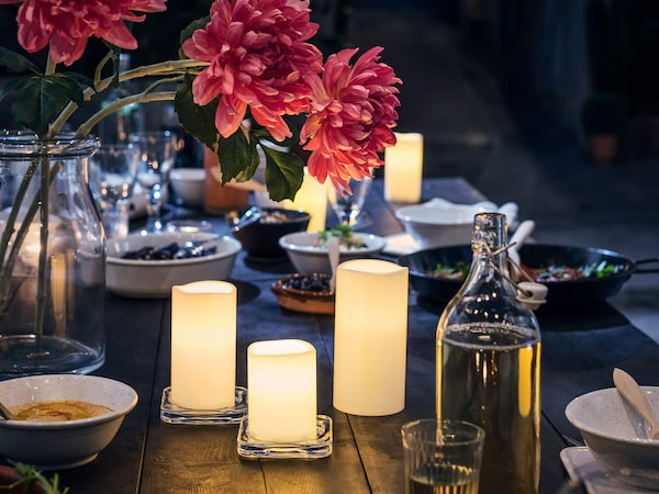 Three lit candles with a vase of flowers, and a table setting for a romantic dinner.