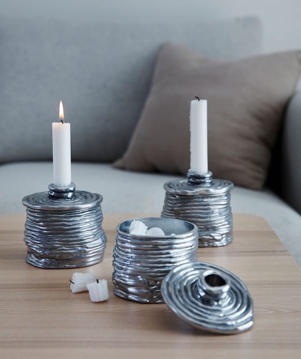 Three metallic candleholders, two with candles and the third – demonstrating that it's also a small box – with the lid off.
