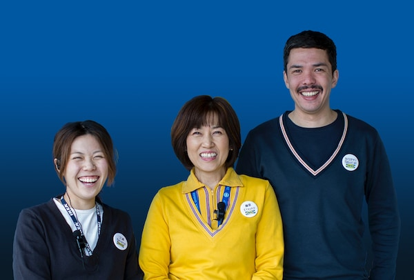 Three of IKEA co-workers are smiling in front of IKEA logo.