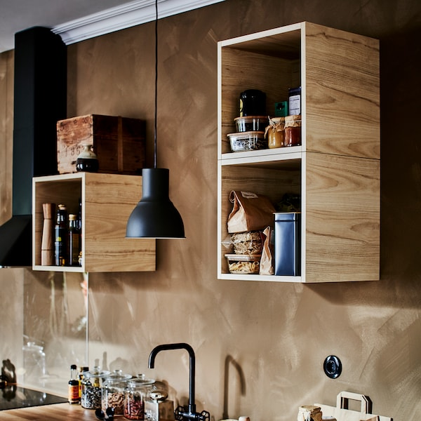 Three open wall cabinets in ash foil, a dark grey pendant lamp, a black kitchen mixer tap and a black extractor hood.