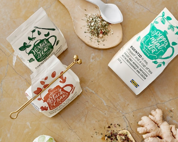 Three packages of IKEA EGENTID teas surrounded by herbs and spices used to give them their flavours.