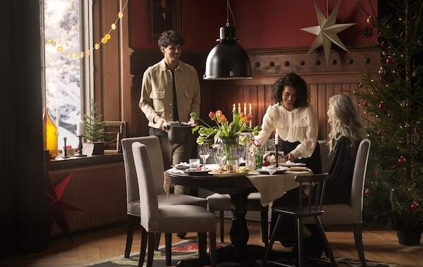 Three people gather round a round INGATORP table decorated with fresh flowers to eat a holiday meal together.