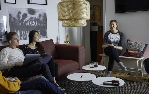 Three people having coffee in a living room.