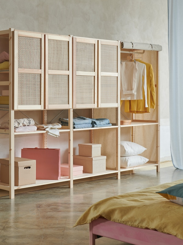 Three sections of IVAR storage system in light pine with four bamboo doors at the top, standing in a bedroom context.