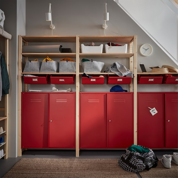 Three shelving units in pine with red drawers and cabinets, two wall lamps mounted on the wall above and a jute rug on the floor in front.
