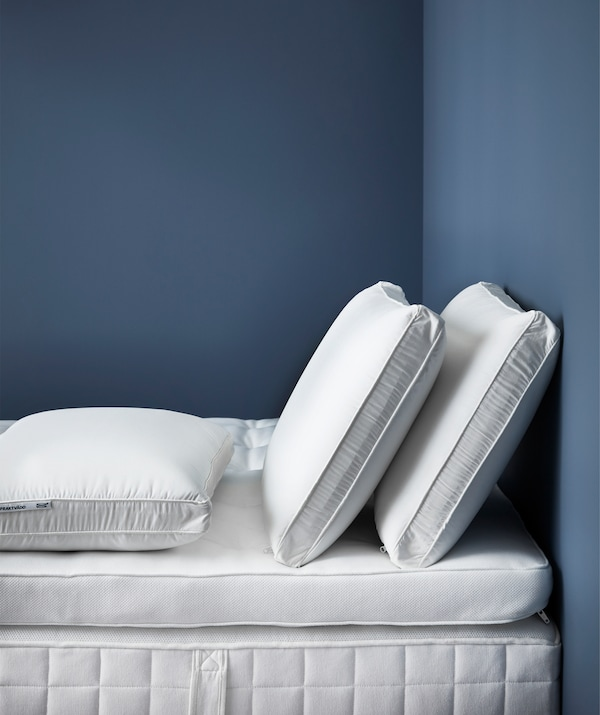 Three side sleeping ergonomic pillows on a mattress base with mattress topper.