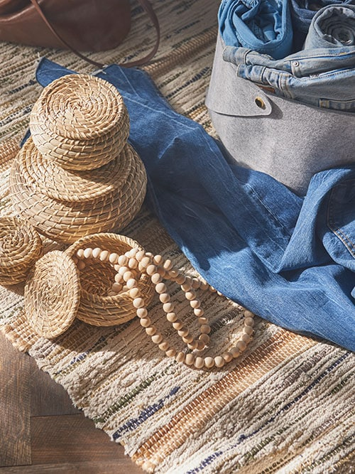 Three small round boxes of natural seagrass, shown next to several pairs of blue jeans and a grey felt storage box.
