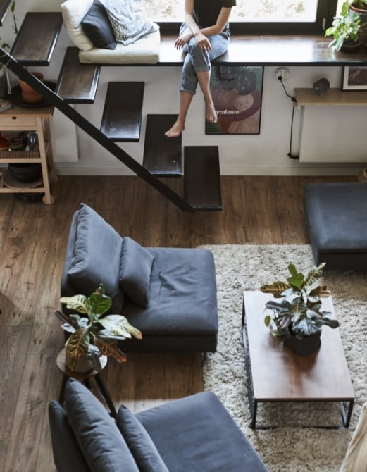 Three sofa sections around a coffee table and an open staircase.