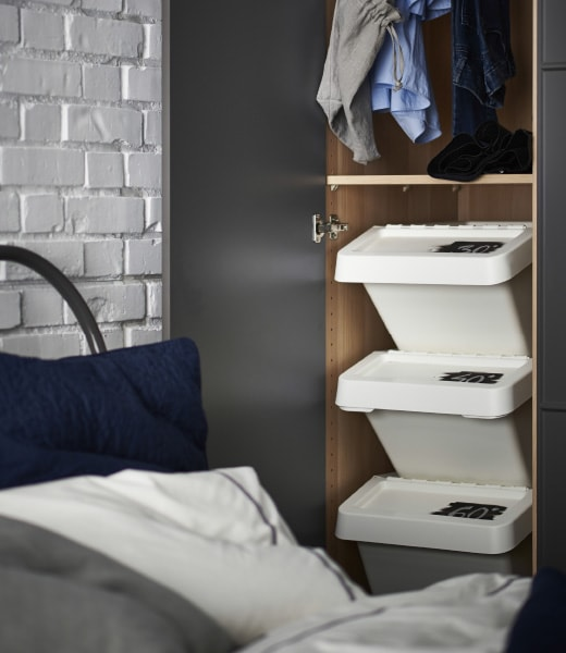 Three stacked IKEA SORTERA boxes are marked with different wash temperatures and used to sort laundry in a closet.