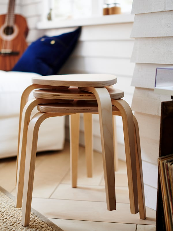 Three stacked KYRRE stools placed by a white clapboard wall, a few feet from a white sofa with a guitar on it.