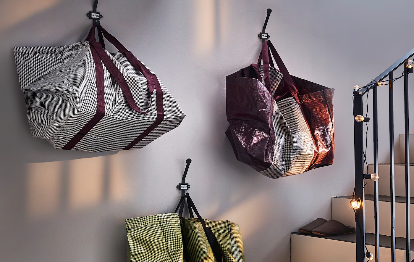 Three storage bags in a mix of greens, whites, purple and yellow hanging from the wall near a staircase.