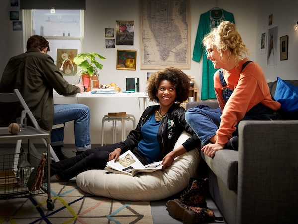 Three teenagers in a small dorm room, smiling and conversing together.