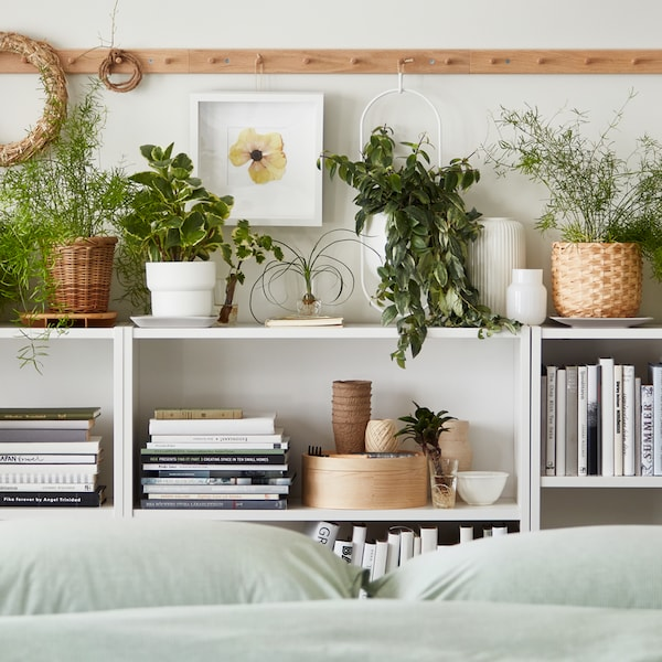 Three white BILLY bookcases against a wall by a bed filled with books, boxes and FEJKA artificial plants in plant pots.