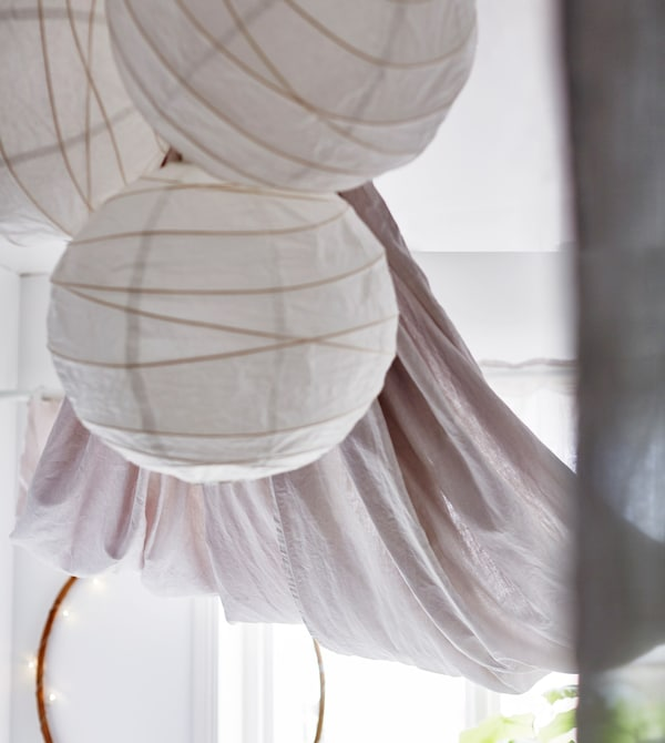 Three white paper lanterns hang from the ceiling in a bright, white dorm room.