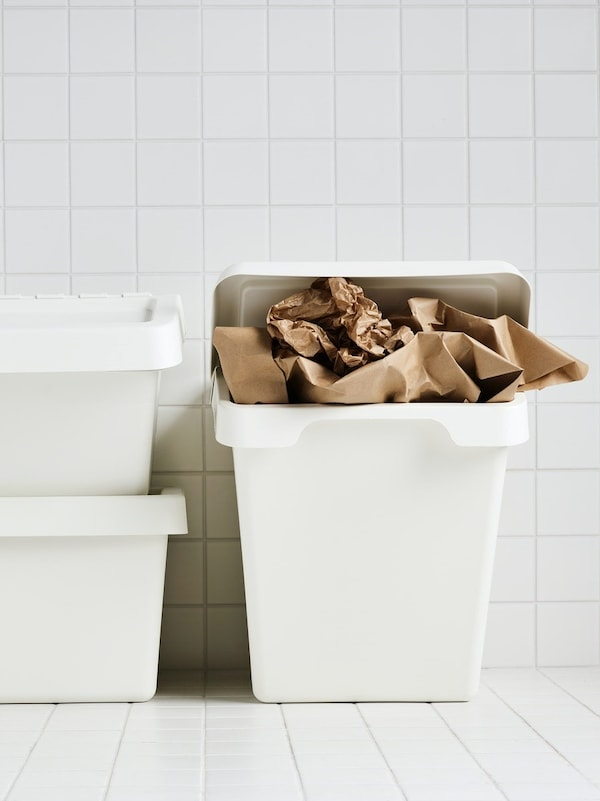 Three white SORTERA bins in a white tiled room where one is stuffed with brown paper.