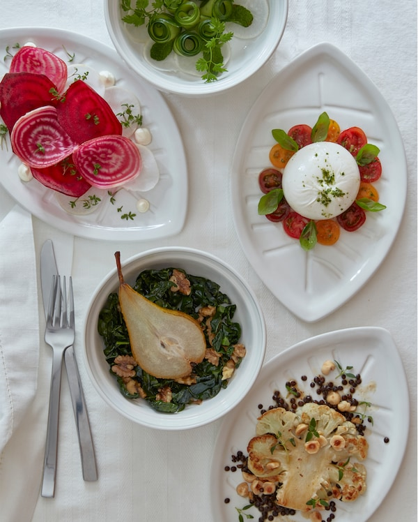 Three white VINTERFEST leaf-shaped side plates and two round serving bowls on a white tablecloth.