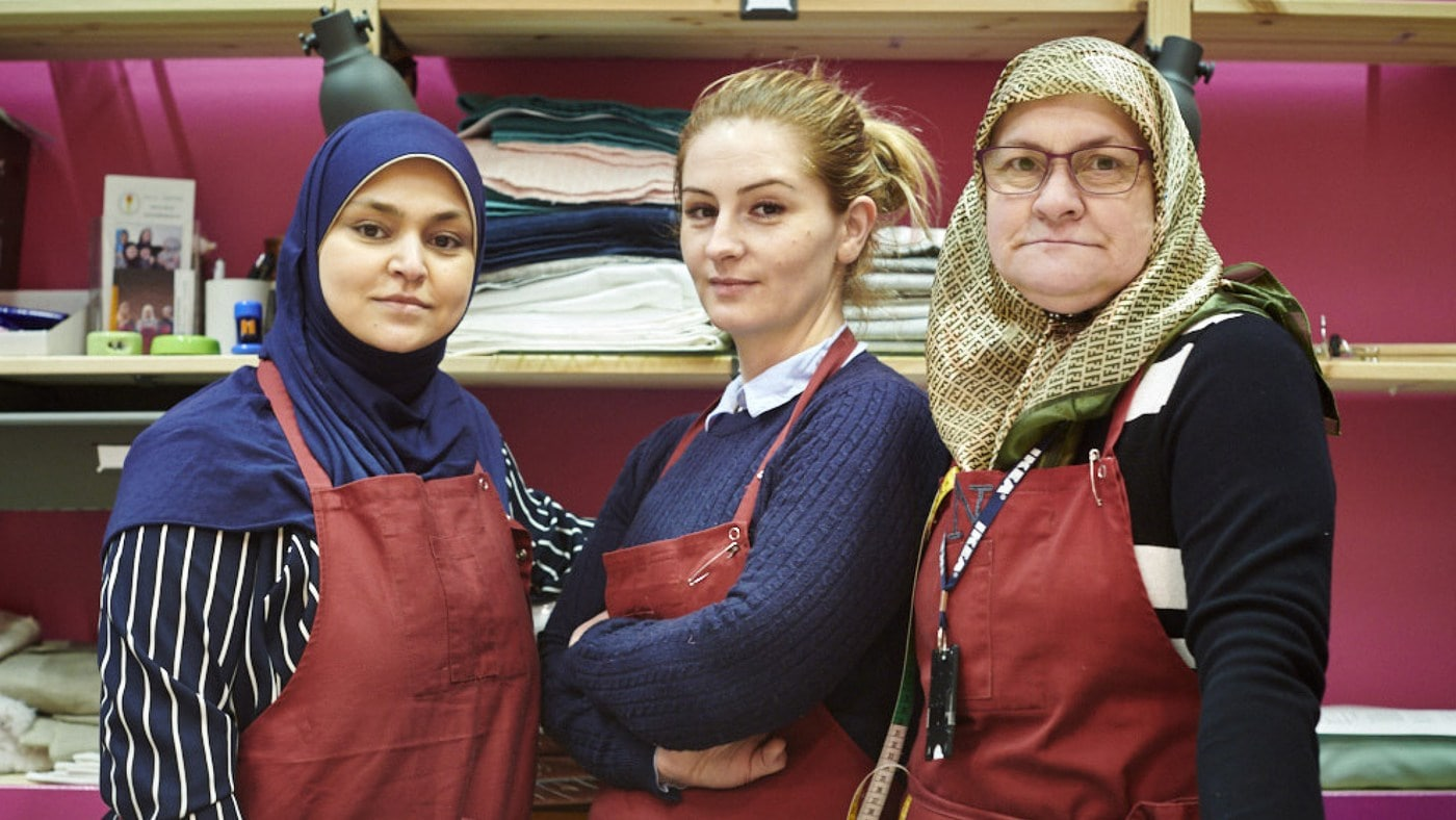 Three women standing confidently in an IKEA store during World Refugee Day, one of the many ways IKEA engages communities.