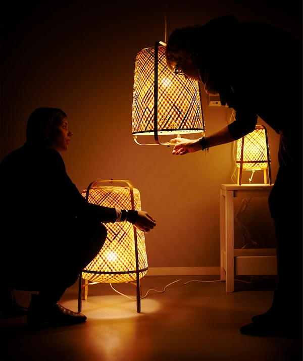 Three woven lamps lit up and two figures in the shadows.