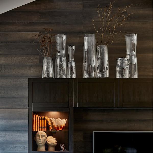 TIDVATTEN üvegvázák egy TV-tároló kombináció tetején, megvilágított polcokkal, könyvekkel és díszekkel.