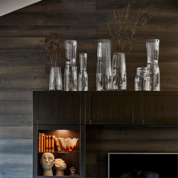 TIDVATTEN vases in clear glass on top of a TV storage combination with illuminated shelves containing books and ornaments.